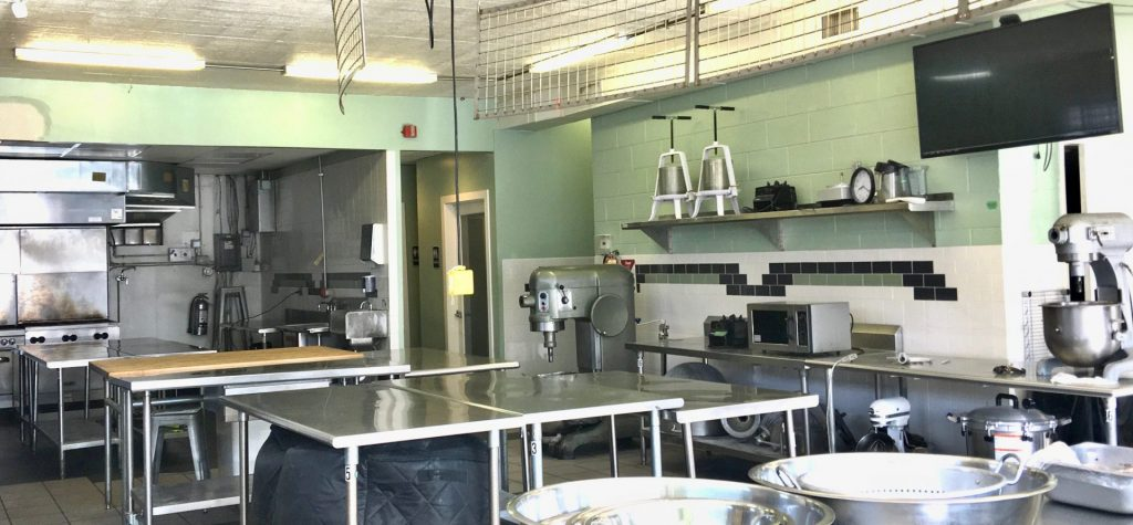 Picture of the kitchen. The walls are pale green with white tile and there are many stainless steel tables.